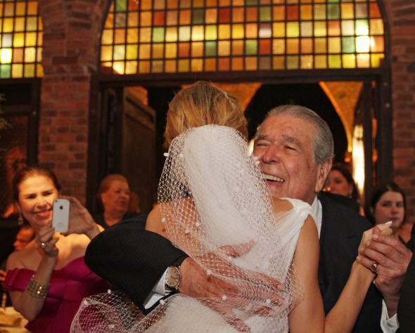 A saudação carinhosa de Ricardo Brennand à noiva. NO fundo, fotografando, Lourdes Brennand