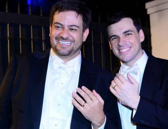 Os noivos Bruno Astuto e Sandro Barros exibindo a aliança, no seu casamento