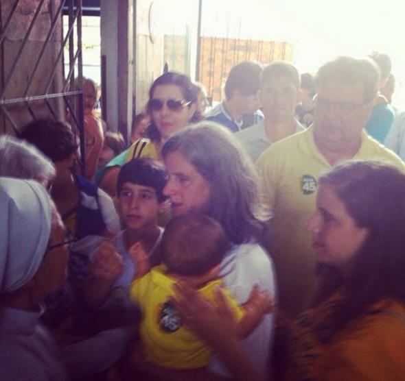 Renata Campos chegando ao Cecosne, com Miguel, para acompanhar a votação de Paulo Câmara. Crédito: Júlia Schiaffarino / DP / D.A Press