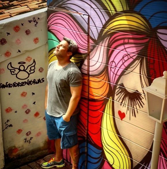 Flávio Barra junto com um de seus trabalhos. Este painel foi pintado em Fernando de Noronha.  Créditos: Reprodução instagram