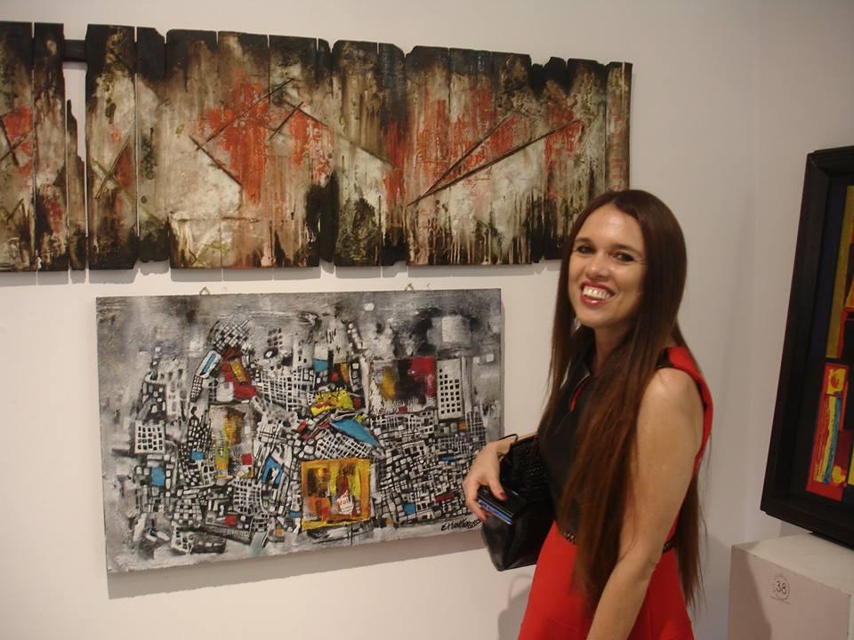Eugênia Harten ao lado de seu quadro, intitulado Metropoli Grigia Créditos: Divulgação