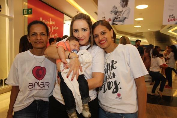 Áurea Negromonte, voluntária da Amar, com Juan no colo e a avó Jacinete Araújo e a mãe Daniele Santos. Crédito: Nando Chiappetta / DP