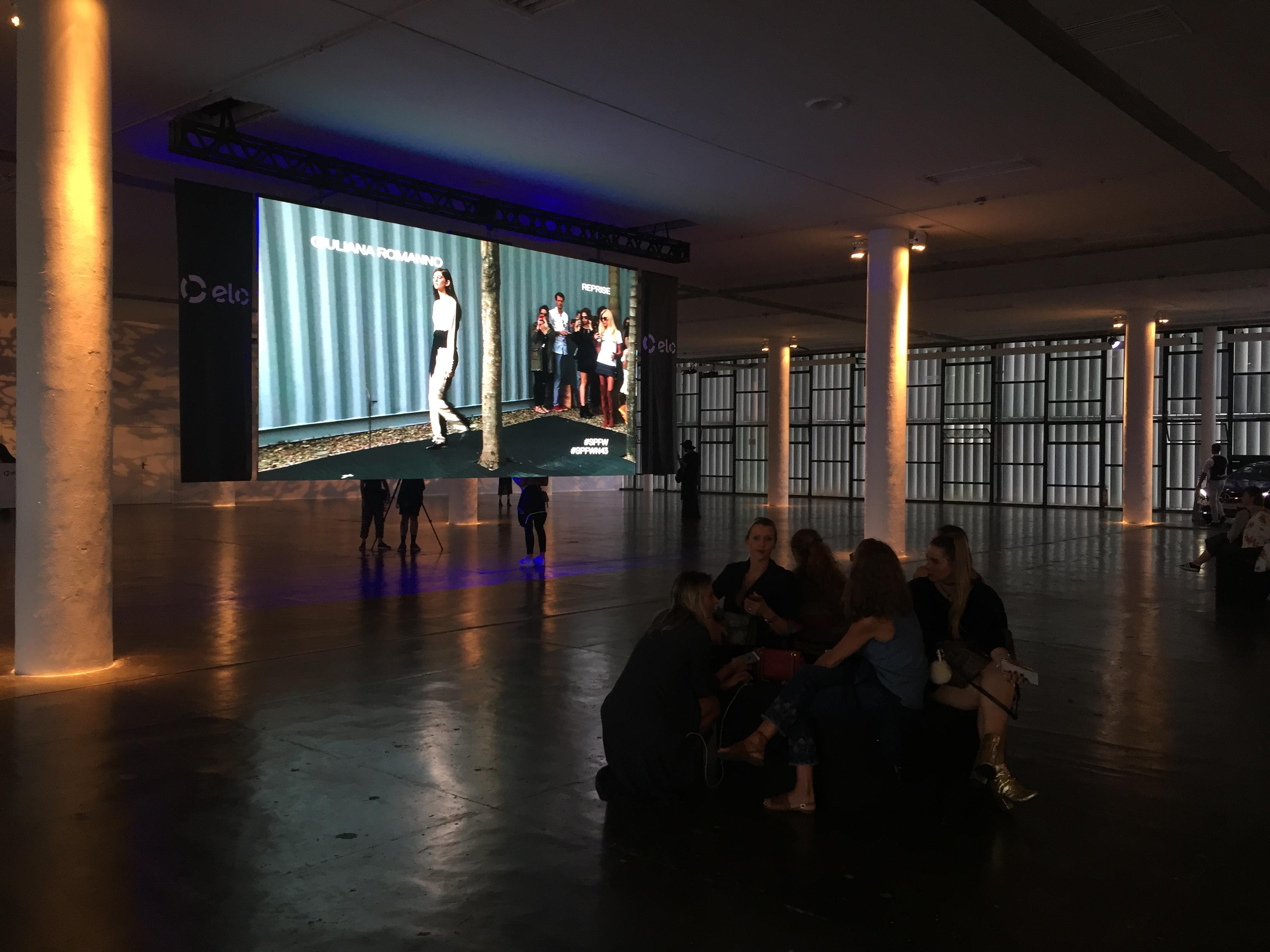 Um telão no centro da Bienal exibe os desfiles em tempo real